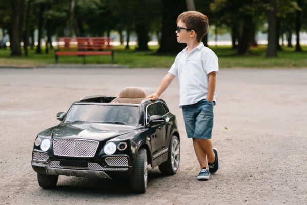 Boy stood with his black electric toy car
